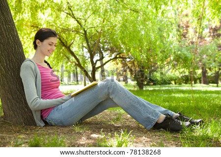 young girl siting next tree and reading book in nature