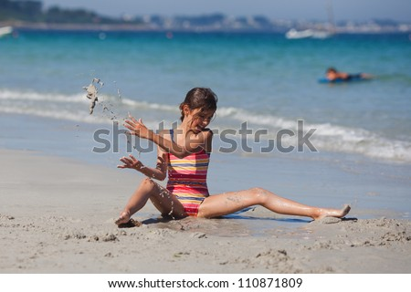 young girl sits at the beach and digs a hole in the sand