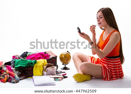 Young girl sits near suitcase. Woman puts makeup on lips. I must look good. This journey will be memorable. - stock photo