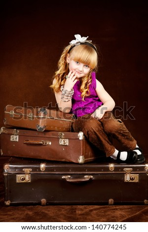Young girl sits on vintage baggage against brown background - stock photo