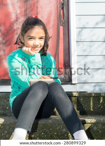 Young girl sits outside writing in her notepad - stock photo