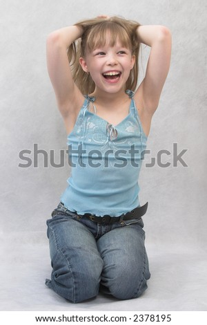 Young girl sits. She wears  top and jeans.