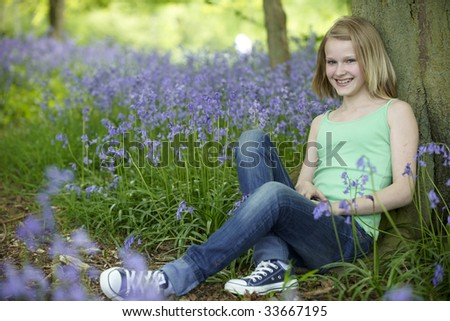 young girl sitting against a tree in a wood full of bluebells