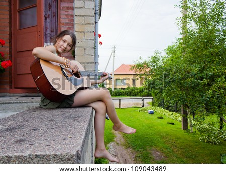 Young girl sitting and playing the guitar outdoors - stock photo