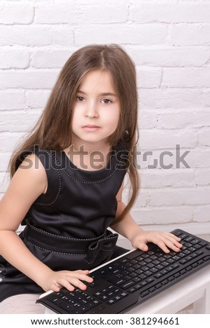 Young girl sitting and typing on a computer keyboard - stock photo