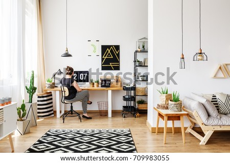 Young Girl Sitting At Desk In A Bright, Minimalist Loft Interior With  Simple White And