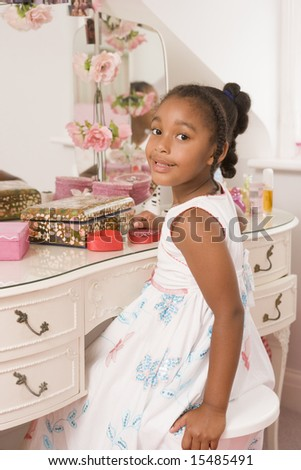 Young girl sitting at mirror in bedroom smiling