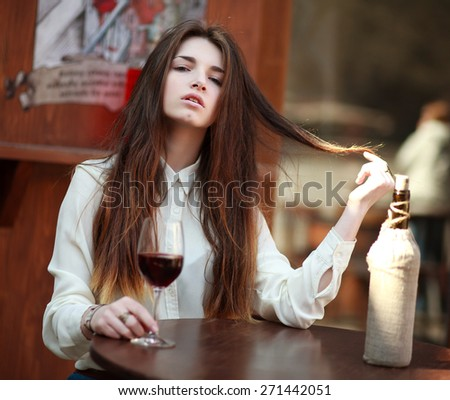 Young girl sitting at table in summer cafe with a glass of wine - stock photo