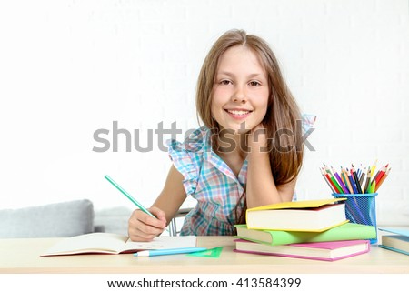 Young girl sitting at the desk and drawing - stock photo