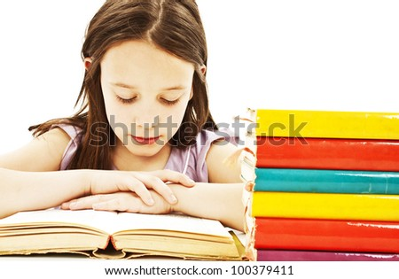 Young girl sitting at the desk and reading book. Isolated on white background. - stock photo