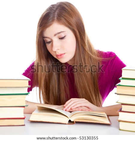 Young girl sitting  at the desk  and reading book. Isolated on white background