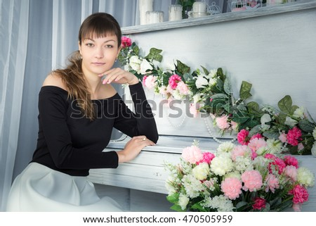 Young girl sitting at the piano, looking at camera