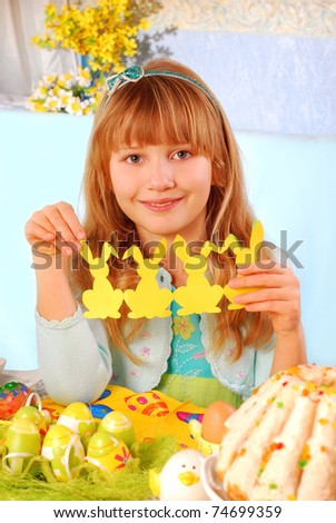 young girl sitting at the table and showing easter decoration with  cut out rabbit made by herself
