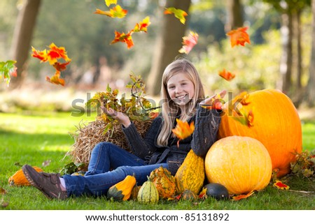 young girl sitting between pumpkins and throwing up some leaves