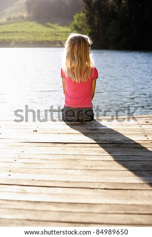 Young girl sitting by lake - stock photo