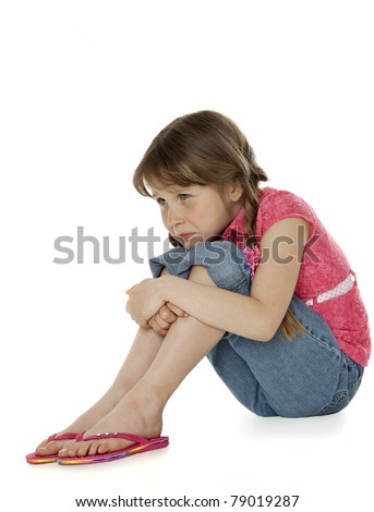 Young girl sitting, hugging knees, sad facial expression, on white. - stock photo