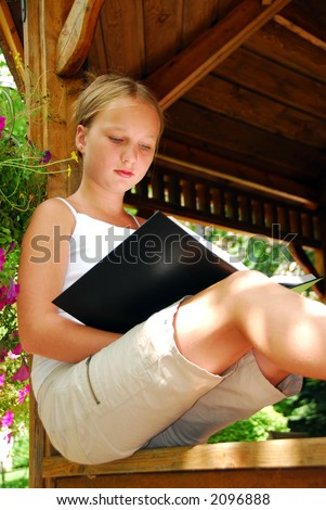 Young girl sitting in a gazebo reading a book - stock photo