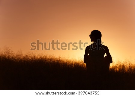 Young girl sitting in a grass field.  - stock photo