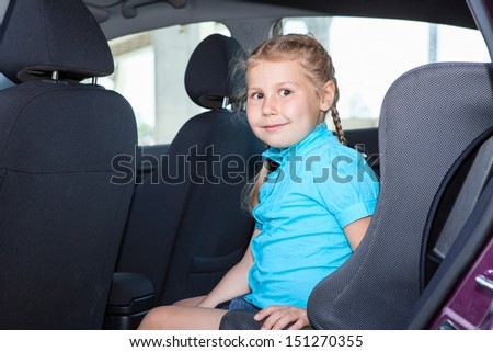 Young girl sitting in car safety seat on back of vehicle - stock photo