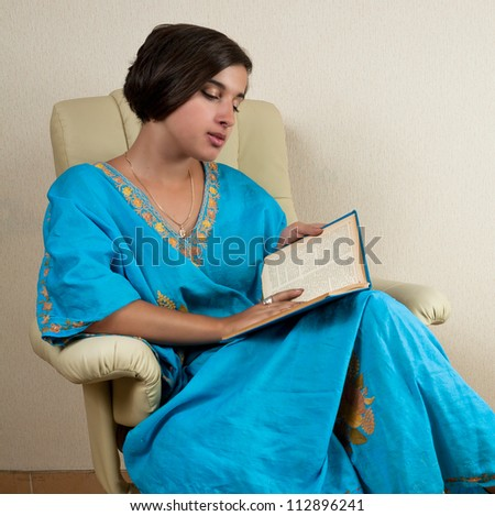 young girl sitting in chair reading book