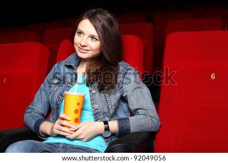 Young girl sitting in cinema and watching movie - stock photo