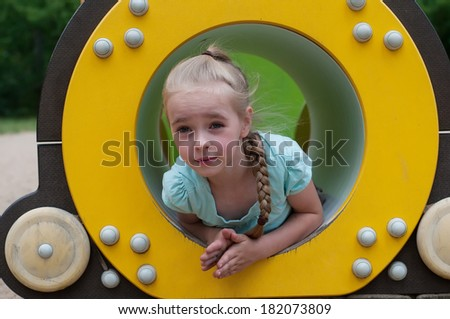 Young girl sitting in crawl tube - stock photo