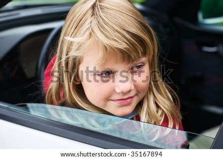 Young girl sitting in driver's seat of car - stock photo