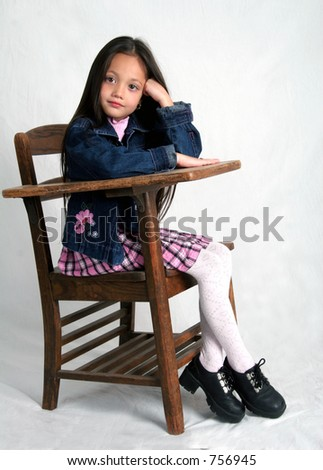 Young girl sitting in school desk - stock photo