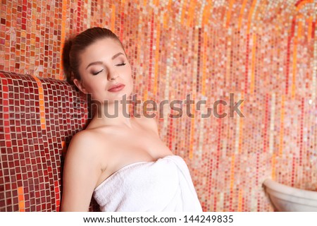 Young Girl sitting in souna wrapped in towel - stock photo