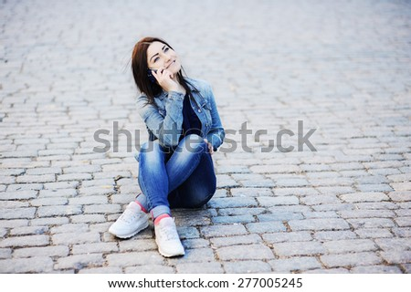 young girl sitting in the street and talking on cell phone