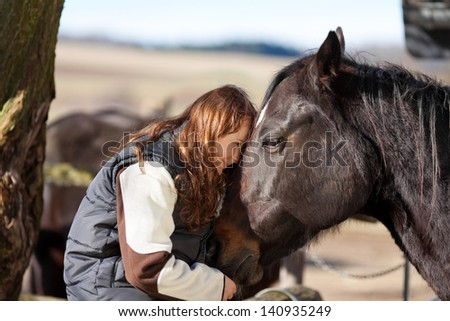 Young girl sitting in the wooden paddock fence pets her dark bay horse - stock photo