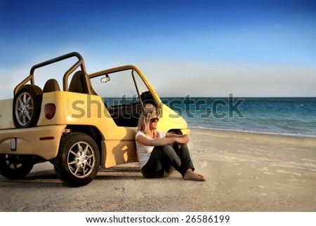young girl sitting on a beach with her car - stock photo
