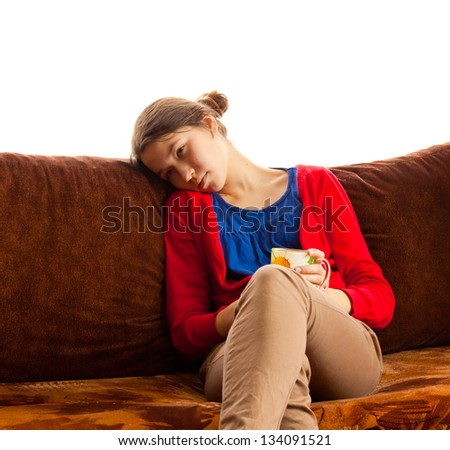 Young girl sitting on a couch with a cup of tea at home in the morning, sleepy, bright light, white background