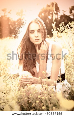 young girl sitting on a flower glade outdoors - stock photo
