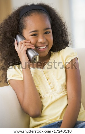 Young Girl Sitting On A Sofa, Talking On A Telephone - stock photo
