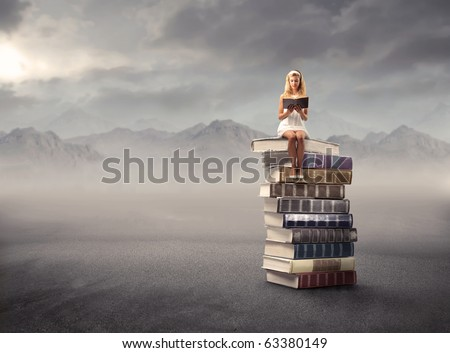 Young girl sitting on a stack of books and reading - stock photo