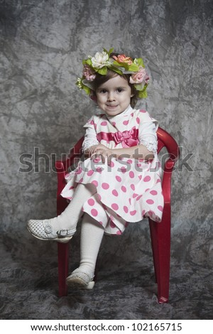 Young girl sitting on a stool - stock photo