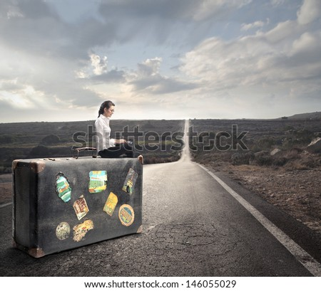 young girl sitting on a vintage suitcase on the road - stock photo
