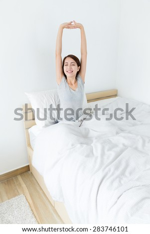 Young girl sitting on bed and hand raised up - stock photo