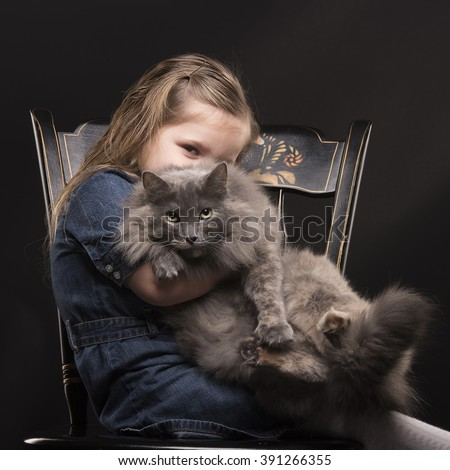 Young girl sitting on chair with a cat on her lap and looking with one eye - stock photo