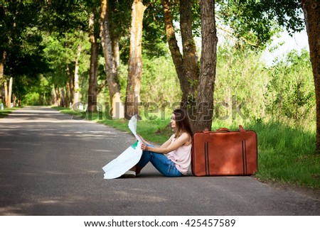 young girl sitting on empty asphalt road near old vintage leather suitcase - stock photo