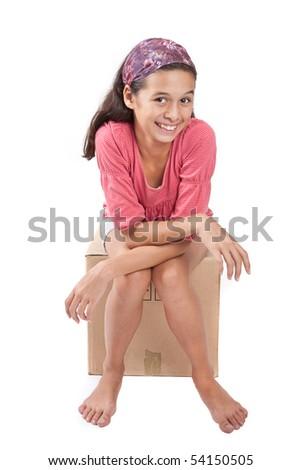 Young girl sitting on empty cardboard box. - stock photo