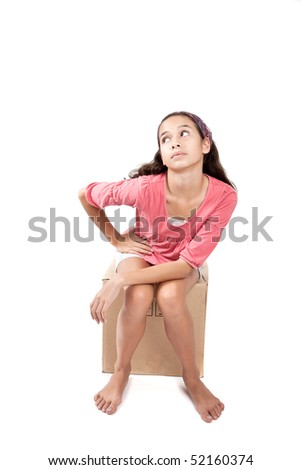 Young girl sitting on empty cardboard box, on white background - stock photo