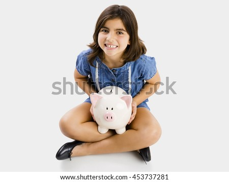 Young girl sitting on floor and holding a piggybank
