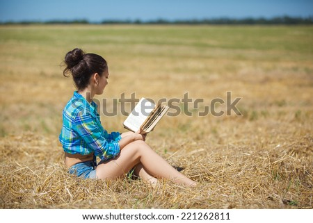 young girl sitting on golden reap wheat in yellow sunset field Woman holding in hands interesting book, reading text  - stock photo
