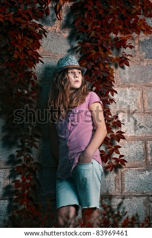Young girl sitting on grassy meadow next to a tree and gnome - stock photo