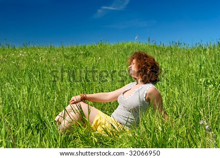 Young girl sitting on green field - stock photo