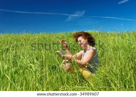 Young girl sitting on green field and reading book