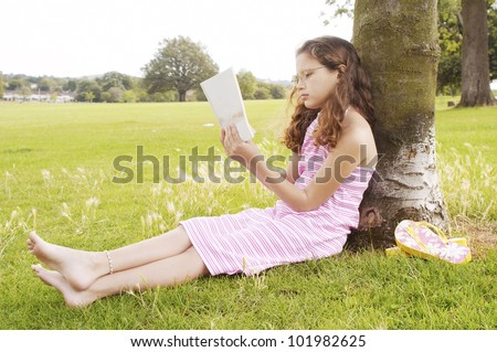 Young girl sitting on green grass in the park and reading a book while leaning on a tree trunk. - stock photo