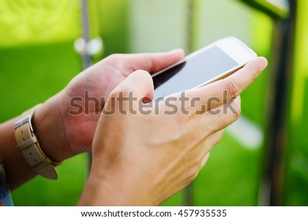 Young girl sitting on green grass with mobile phone.woman using her Mobile Phone. female student reading text messages on her mobile phone.Soft focus